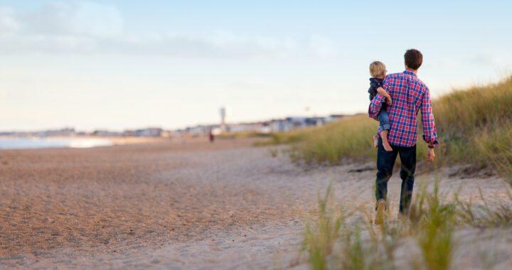 Vanhempi, lapsi sylissään, rannalla