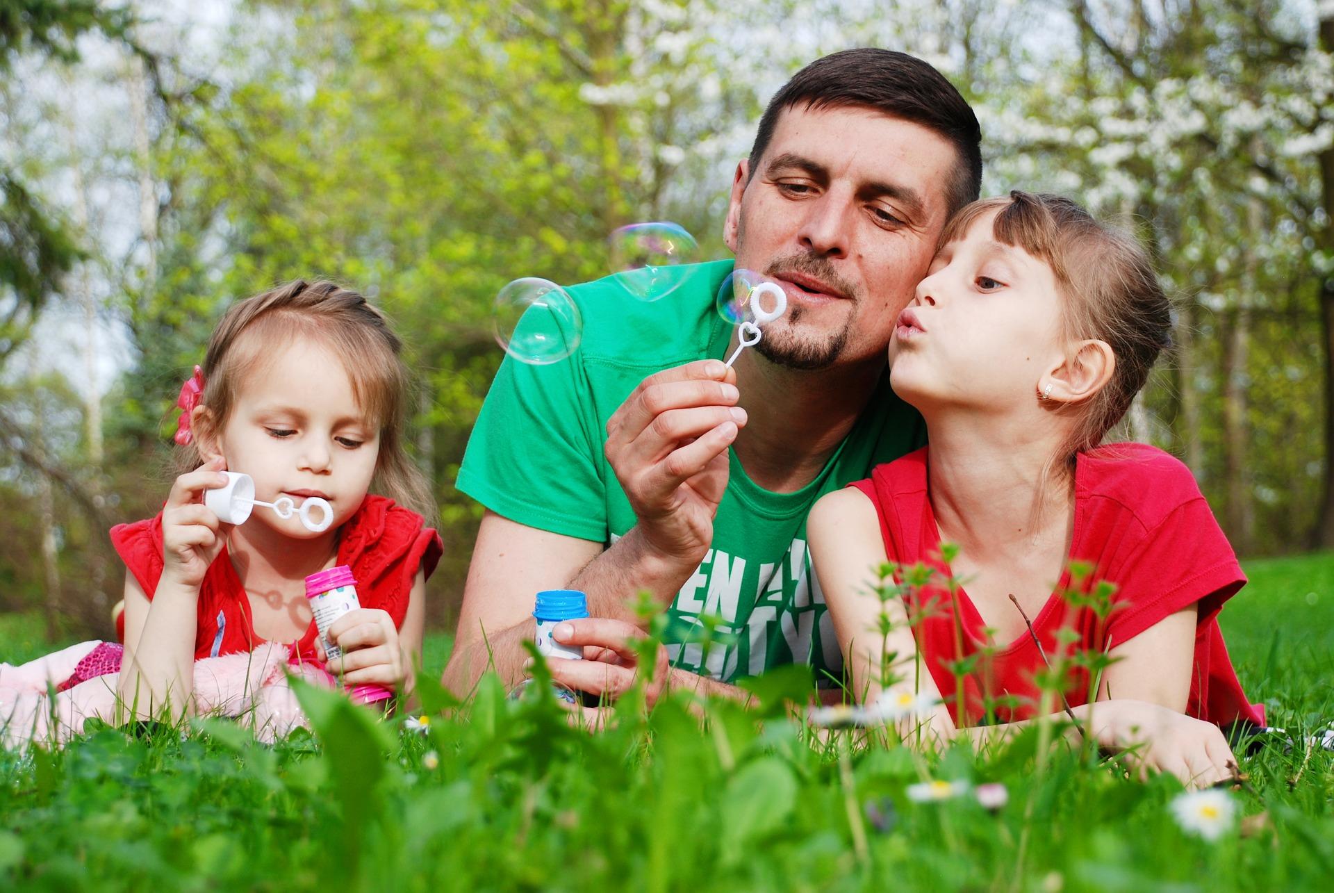 Vanhempi lastensa kanssa enurmikolla puhaltelemassa saippuakuplia